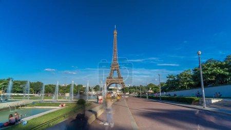 Photo pour Coucher de soleil vue de la Tour Eiffel timelapse hyperlapse avec fontaine dans les Jardins du Trocadéro à Paris. Longues ombres. Gens se promener. La Tour Eiffel est l'un des monuments plus emblématiques de Paris. - image libre de droit