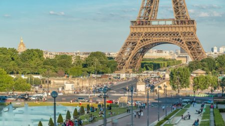Sunset view of Eiffel Tower timelapse with fountain in Jardins du Trocadero in Paris, France. Long shadows. People walking around. Eiffel Tower is one of the most iconic landmarks of Paris.