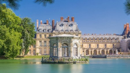 Photo for Beautiful Medieval landmark - royal hunting castle Fontainbleau timelapse hyperlapse with reflection in water of pond. Palace of Fontainebleau - one of largest royal chateaux in France, UNESCO World Heritage Site. - Royalty Free Image