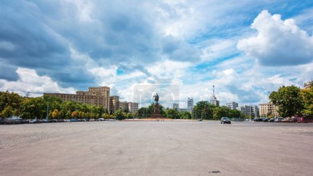 Pedestrians walk on Freedom Square at sunny day ti...