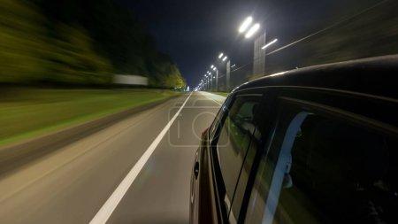 Foto de Drivelapse del lado del coche en movimiento en una noche carretera timelapse hyperlapse, carretera con luces reflejadas en coche a alta velocidad. Ritmo rápido de una ciudad moderna. - Imagen libre de derechos