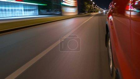 Foto de Drivelapse del lado del coche rápida en movimiento en una avenida de noche en una ciudad timelapse hyperlapse, carretera con luces reflejadas en el coche a alta velocidad. Ritmo rápido de una ciudad moderna. - Imagen libre de derechos