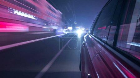 Foto de Drivelapse urbano buscar de coche rápida que conduce en una avenida de noche en una ciudad timelapse hyperlapse, carretera con luces reflejadas en el coche a alta velocidad. Ritmo rápido de una ciudad moderna. - Imagen libre de derechos