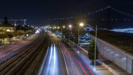 Photo for Car light trails . Night traffic view of India Avenue in Belem zone in Lisbon Portugal. Illuminated bridge on background - Royalty Free Image