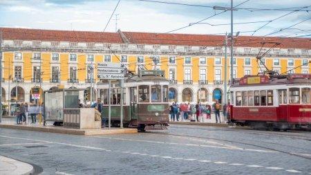 Photo pour Les vieux tramway Lisbonne s'arrête sur la place du Commerce dans la vieille ville. Célèbre vintage voyage touristique. Scène rue de la ville de bâtiments architecture colorée - image libre de droit