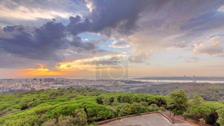 Photo pour Sunrise panoramique vue sur Lisbonne et Almada du point de vue dans la matinée de Monsanto. Vue aérienne de haut avec des nuages colorés et des rayons de lumière - image libre de droit