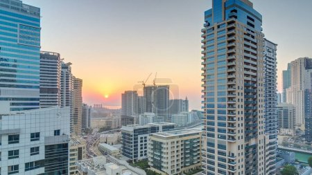 Photo for Aerial view of Dubai Marina from a vantage point at sunset timelapse. Modern skyscrapers and residential towers illuminated by warm evening light - Royalty Free Image