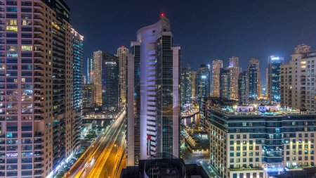 Photo for Aerial view of Dubai Marina from a vantage point night timelapse. Modern skyscrapers and residential towers illuminated with glowing windows. Traffic on the road - Royalty Free Image