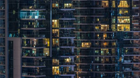 Photo for Glowing windows in multistory modern glass residential building light up at night timelapse. People in apartments. Houses illuminated at evening. Dubai Marina, UAE. - Royalty Free Image