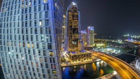 Photo pour JBR et Dubai marina nuit aériennes timelapse. Illuminée de tours modernes et de gratte-ciels, le trafic sur le pont, les yachts et les bateaux flottant sur le canal - image libre de droit