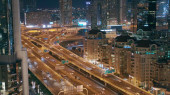 Aerial view of illuminated skyscrapers and road junction in Dubai