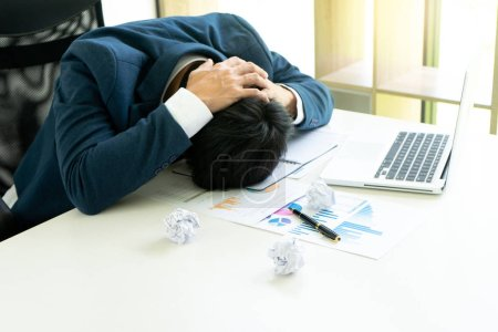 businessman sit at the table fill sad and headache , concept business failure or problem