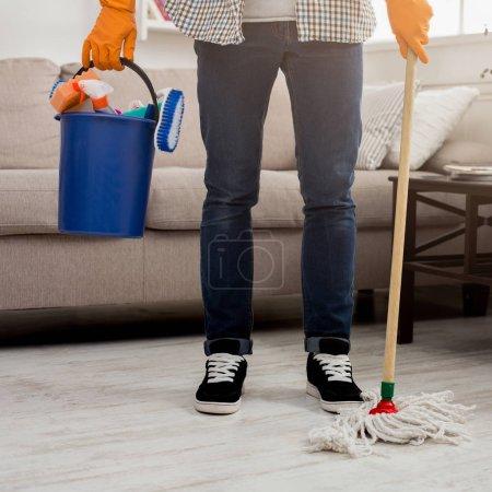 Photo pour Un homme méconnaissable prêt à nettoyer. Récolte de jambes mâles avec vadrouille et seau en plastique avec des fournitures de nettoyage debout près. Ménage et nettoyage fond de service, espace de copie - image libre de droit