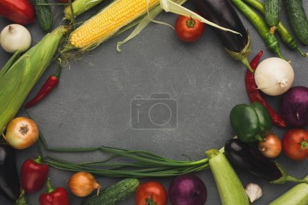 Photo for Frame of fresh organic vegetables on grey background. Healthy natural food on rustic wooden table with copy space. Corn, eggplant, onion, pepper, tomatoe and other cooking ingredients top view - Royalty Free Image