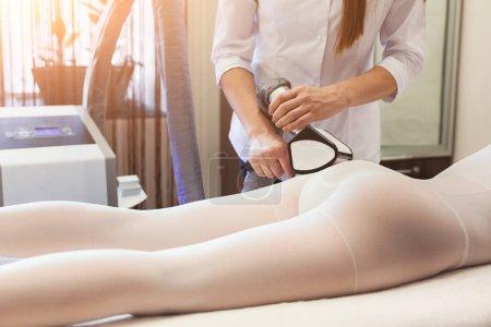 Photo pour Le masseur fait un massage quincaillerie sur les jambes des patients en costume blanc, dans un salon de beauté. Traitement, soins, concept beauté - image libre de droit