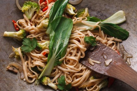 Photo for Asian restaurant food. Vegetarian stir fry with noodles, broccoli and green spinach cooking on grey plate closeup - Royalty Free Image