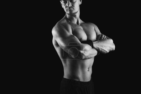 Photo for Strong athletic man, bodybuilder. Naked torso, muscular body. Strong chest and shoulder muscles. Studio shot on black background, low key. Bodybuilding concept, black and white image - Royalty Free Image