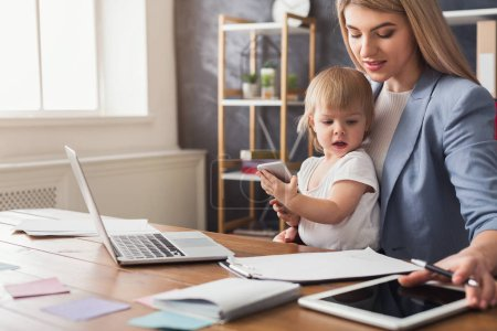 Photo for Happy beautiful business mom working with documents in office while her cute baby holding smartphone. Business, motherhood, multitasking and family concept. - Royalty Free Image