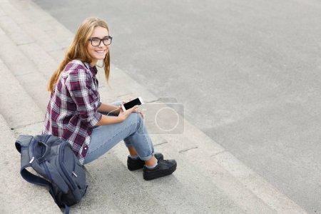 Photo pour Jeune femme souriante assise dans les escaliers de l'université, écoutant de la musique avec des écouteurs à l'extérieur. Repos, concept d'éducation et de détente, espace de copie - image libre de droit