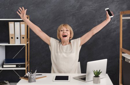 Photo for Happy mature businesswoman in office. Accountant sitting with raised arms, enjoying new achievement - Royalty Free Image