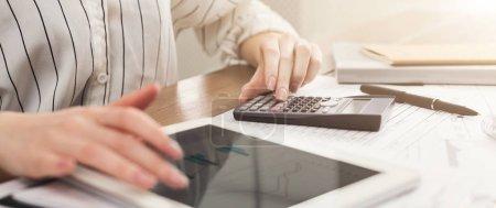 Photo pour Femme compte les finances, en utilisant une calculatrice et une tablette avec écran blanc. Application comptable. Méthodes anciennes et modernes de comptabilisation, espace de copie - image libre de droit