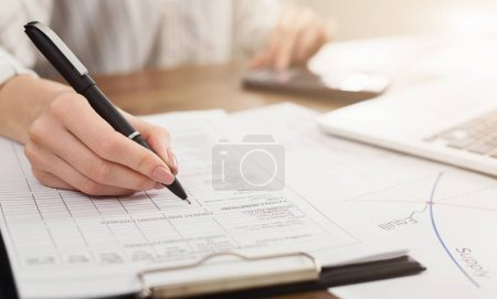 Photo for Female hand with pen and business report. Woman accounting and fill in financial form, copy space - Royalty Free Image