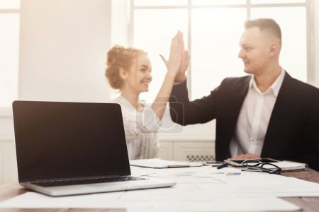 Blank laptop and happy man and woman doing high-five