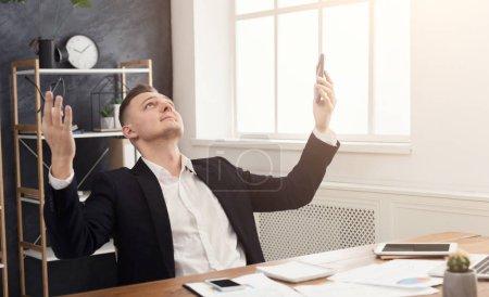 Photo pour Homme d'affaires satisfait heureux enfin de terminer le travail avec calculatrice et rapports au bureau, lève les mains, détente après une dure journée de travail, espace de copie - image libre de droit