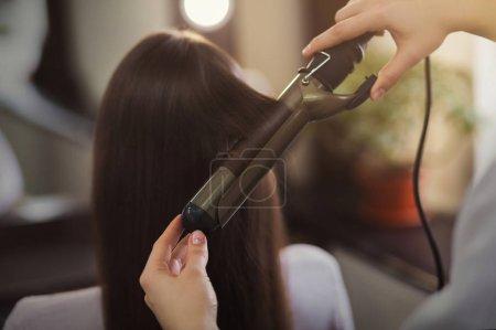 Photo pour Coiffeur utilisant le fer à friser à longs cheveux bruns dans le salon de beauté - image libre de droit
