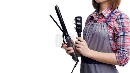 Photo for Female hairdresser holding hair straightener and brush isolated on white backgropund - Royalty Free Image