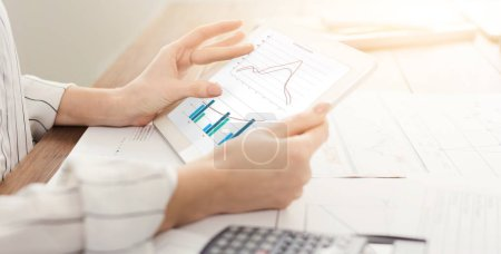 Photo for Close-up of woman looking at graph on digital tablet, analyzing financial report, copy space - Royalty Free Image