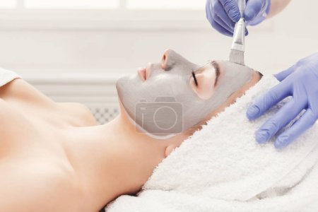 Photo for Face mask, spa beauty treatment, skincare. Woman getting facial nourishing mask by beautician at spa salon, side view, closeup - Royalty Free Image