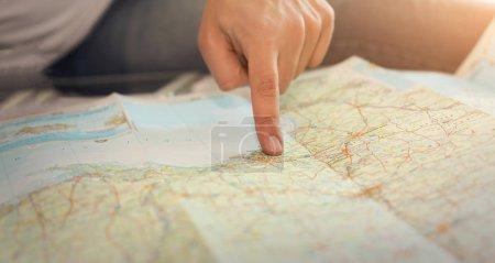 Photo pour Gros plan montrant un mans doigt à un endroit sur une carte de papier. Planification d'itinéraire de voyage de l'homme - image libre de droit