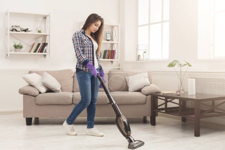 Young woman cleaning house, washing floor with vac...