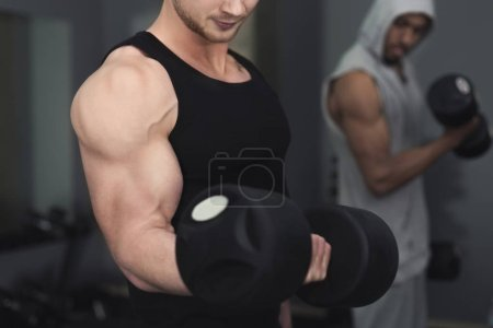 Photo for Young unrecognizable muscular bodybuilder doing heavy deadlifts in modern fitness center. Strong man exercising with dumbbells at gym, copy space, closeup - Royalty Free Image