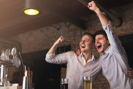 Photo for Happy friends cheering for favorite team win, drinking beer and celebrating goal together in pub, copy space - Royalty Free Image