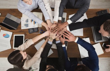 Photo for United coworkers standing with their hands together above workplace in modern office, celebrating successful project, top view, teambuilding and unity background - Royalty Free Image