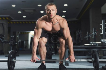 Photo for Young naked muscular bodybuilder doing heavy deadlifts in modern fitness center. Strong man exercising with dumbbell at gym, copy space - Royalty Free Image