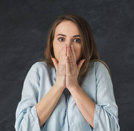 Photo for Shocked young woman closing mouth in full disbelief. Surprised girl portrait, gray background. Omg, wtf, human emotions concept - Royalty Free Image