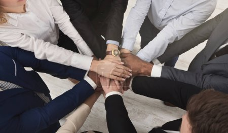 Photo for United coworkers standing with their hands together in modern office, celebrating victory, top view, teambuilding and unity background - Royalty Free Image