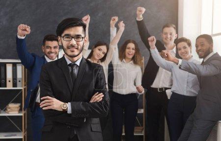 Photo pour Homme d'affaires confiant avec les mains croisées debout avec son équipe à succès dans le bureau. Succès, leadership et concept de motivation, espace de copie - image libre de droit
