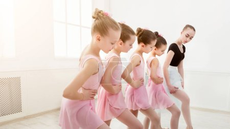 Photo for Young ballet teacher and students ballerinas in dance class. Girls are engaged in choreography in the ballet school, copy space - Royalty Free Image