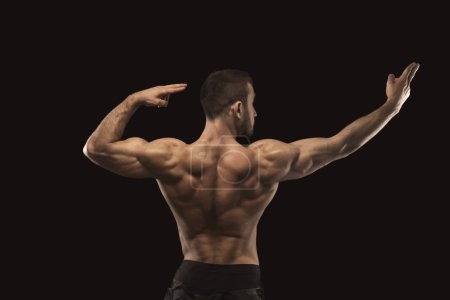 Photo for Strong athletic man showing big biceps and muscular body, standing in bodybuilder competitive posture, back view. Studio shot on black background. Bodybuilding concept - Royalty Free Image