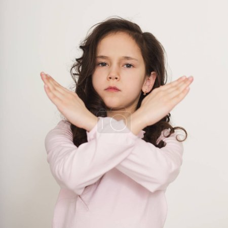 Photo pour Petite fille affichage de panneau d'arrêt avec les bras croisés, refuser le geste - image libre de droit