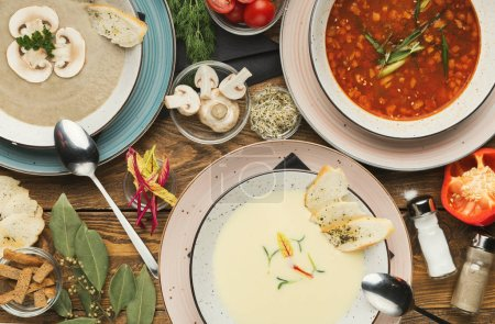 Photo for European cuisine variety. Three different soups on wooden table, top view - Royalty Free Image