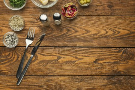 Photo for Empty wooden table with knife and fork and seasonings, top view, copy space - Royalty Free Image