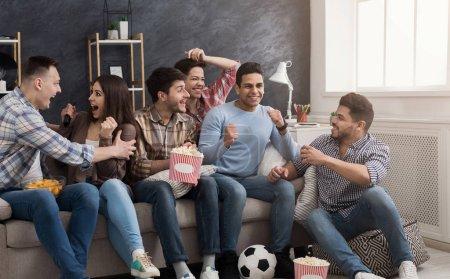 Photo pour Amis excités de s'amuser en regardant le match de football et de manger à la maison - image libre de droit