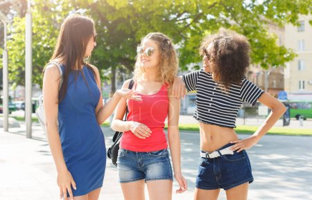 Photo for Outdoors portrait of three female multiethnic friends. Girls in casual clothes having a walk in city in summer and having fun, copy space. Urban lifestyle, friendship concept - Royalty Free Image