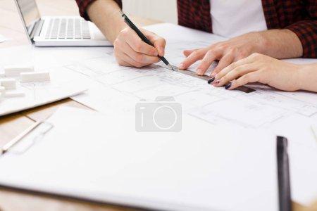 Foto de Dos colegas hablando de proyecto arquitectónico, trabajo con planos en el interior del lugar de trabajo moderno, espacio de copia, closeup - Imagen libre de derechos