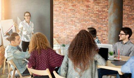 Photo pour Femme gaie top manager faire une présentation à des collègues, montrant tableau financier croissant sur tableau blanc, espace de copie - image libre de droit